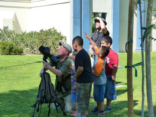 Dave Hursh, assisted by Zach Weber, gets great views of the parakeets for the kids in the park.